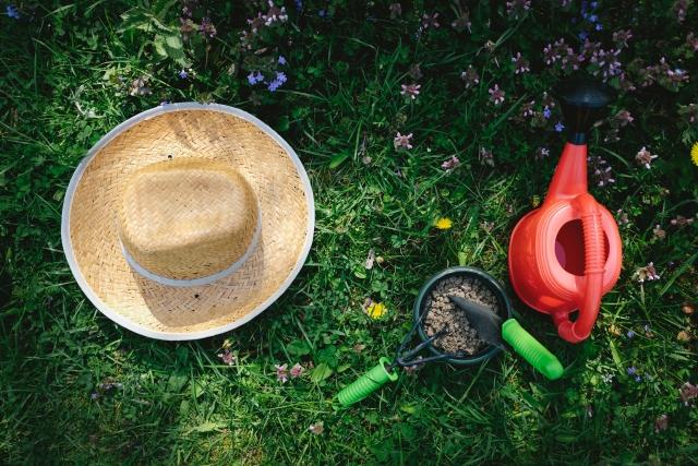 芝生の上の麦わら帽子とガーデニングセット