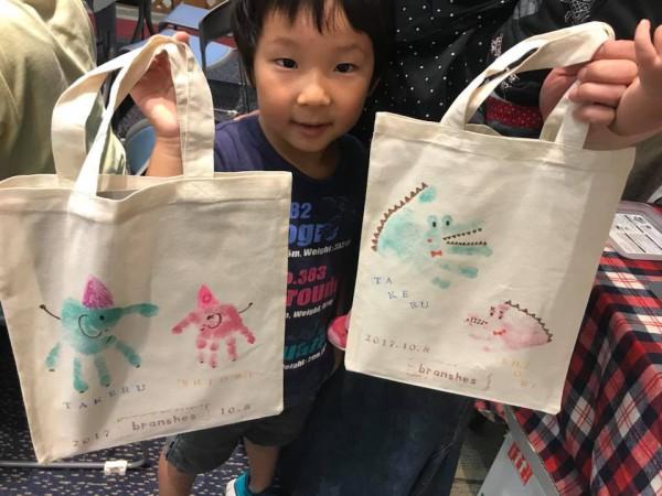 両手にバッグを持つ子ども