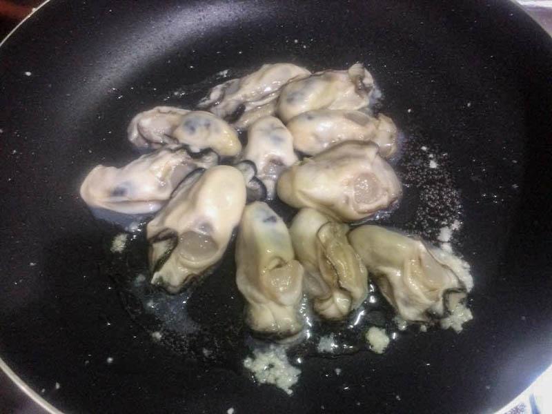 フライパンで牡蠣を炒める