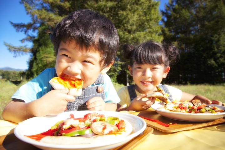 ピザを食べる子どもたち