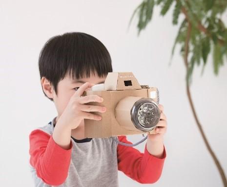 ダンボールのカメラで遊ぶ子ども
