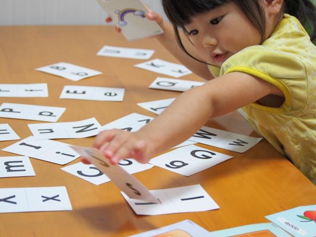 アルファベットのカードで遊ぶ子ども