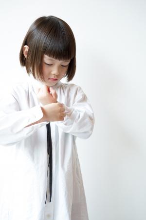 袖のボタンをとめる女の子
