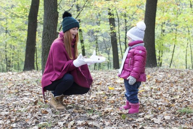秋の森の中にいるママと子ども
