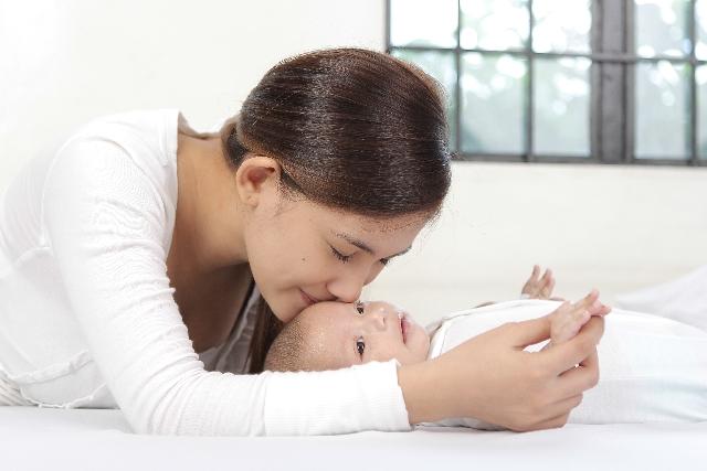 寝ている赤ちゃんにキスをする母親