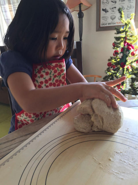 子どもがパンの生地をこねる