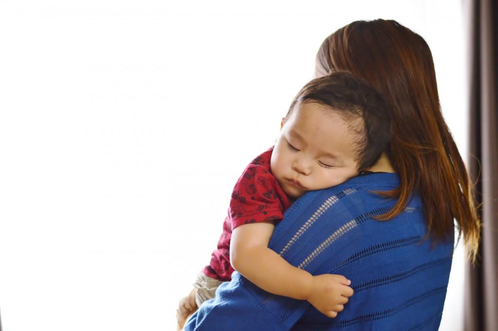 寝てる男の子を抱っこするママ