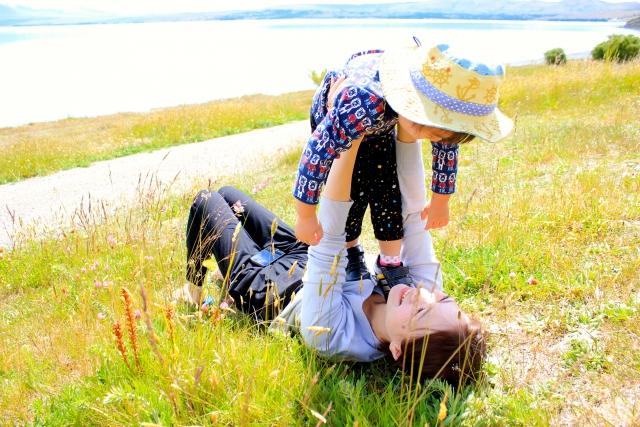 川原で子どもを抱き上げるママ