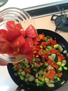 炒めた野菜にトマトを入れる