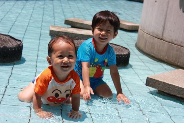 浅いプールで遊ぶ子ども