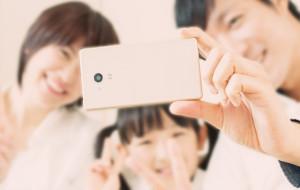 スマートフォンで自撮りをする家族
