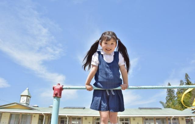 鉄棒を持って笑う女の子