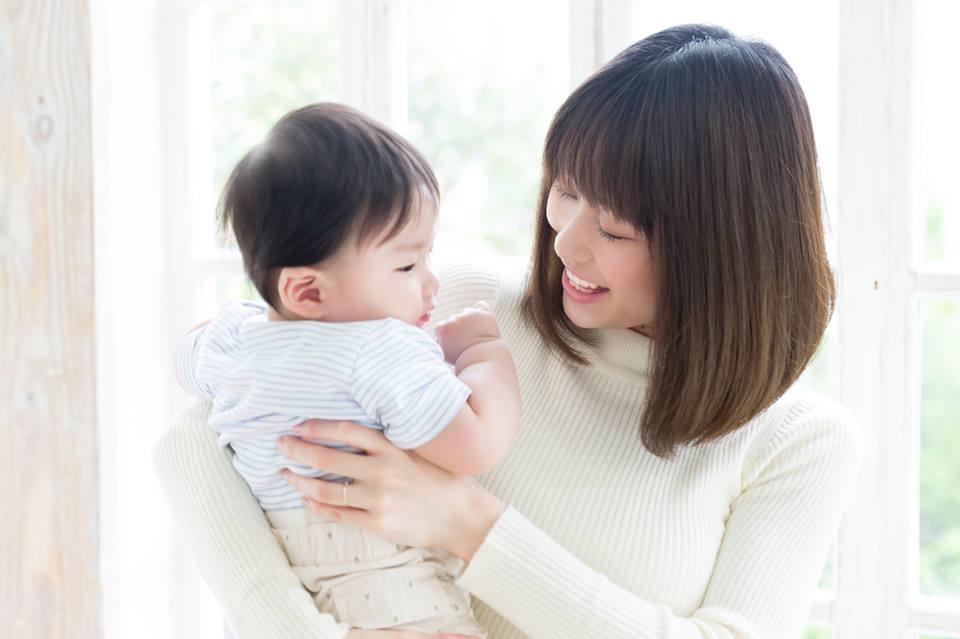 赤ちゃんを抱いて微笑むママ