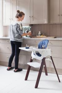 チェアの横で台所仕事をする女性