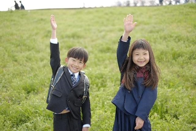 手を挙げる男の子と女の子