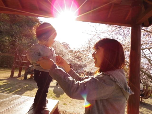 公園のテーブルにいるママと子ども
