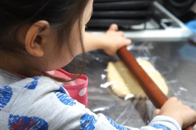 綿棒でパン生地を伸ばす子ども