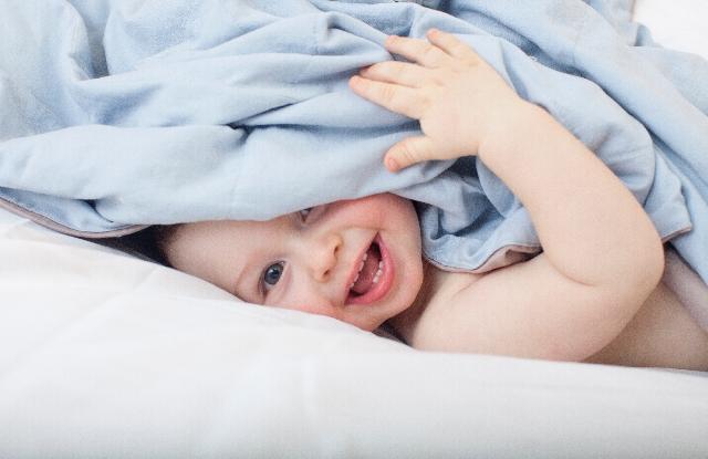 毛布から顔を出す赤ちゃん