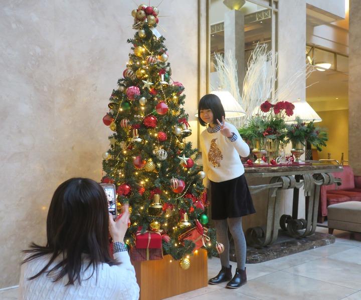 クリスマスツリーの前で撮影する女の子