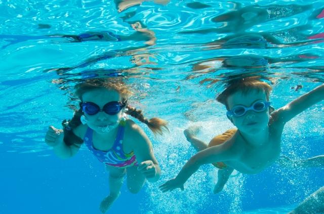 プールで泳ぐ男の子と女の子