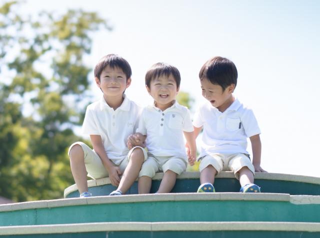 公園の遊具の上の男の子3人
