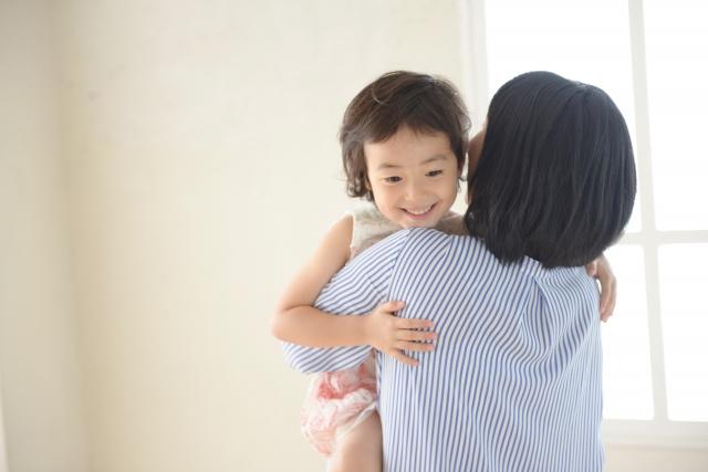子どもを抱っこするママ
