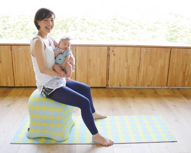 ジェリーフィッシュチェアに座る赤ちゃんを抱いた女性