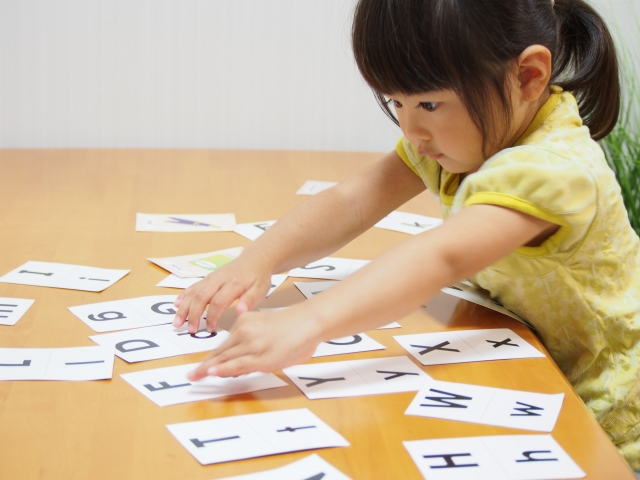 アルファベットのカードで遊ぶ女の子