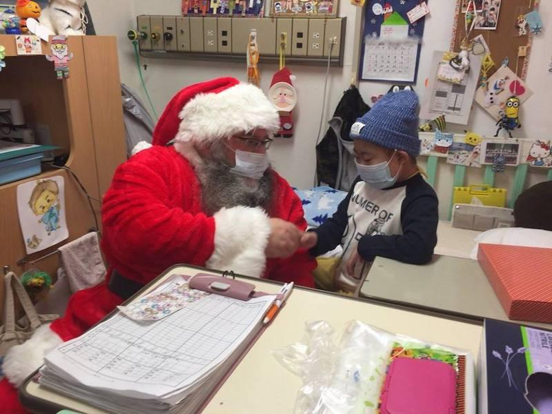 病室でプレゼントをもらう子ども