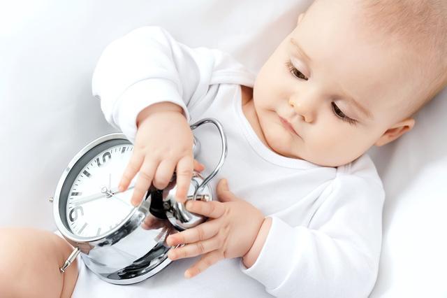 時計で遊ぶ赤ちゃん