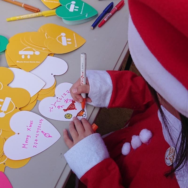 サンタ衣装でメッセージを書く子ども