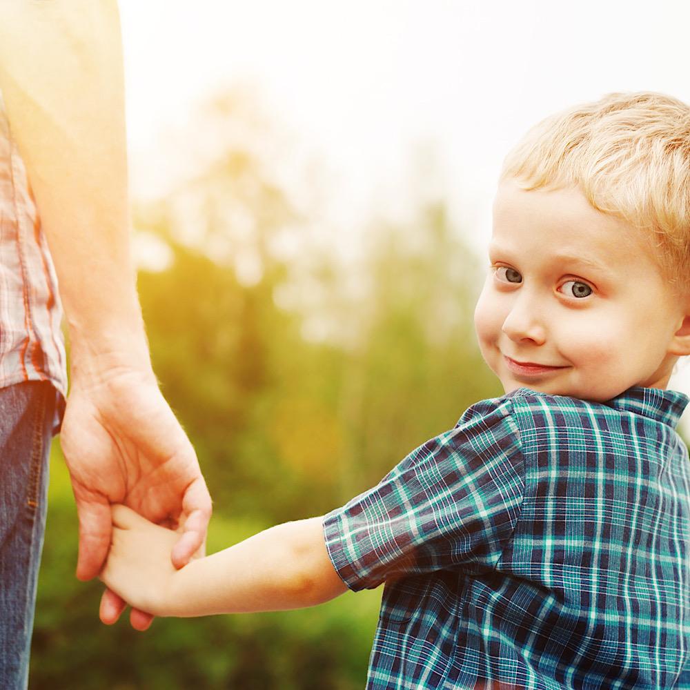 ママと手を繋いで振り向く男の子