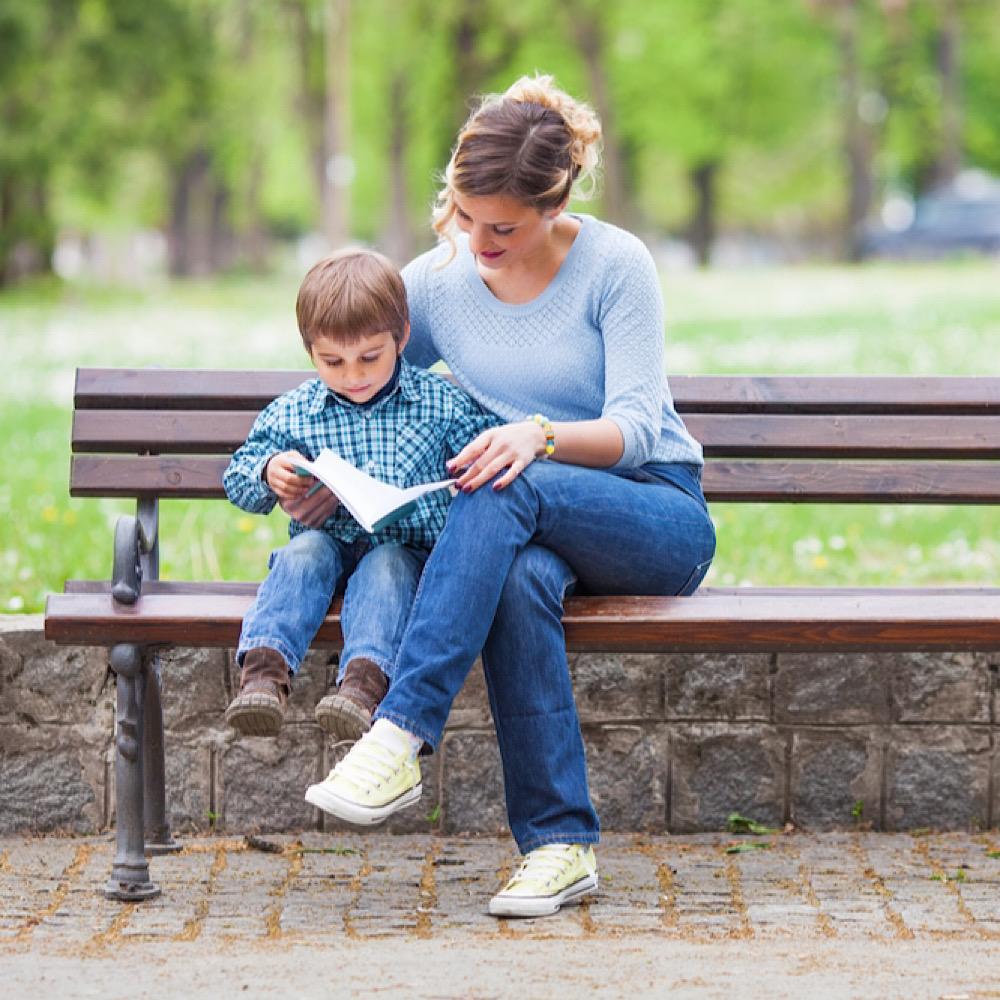 公園で子供に本を読むママ