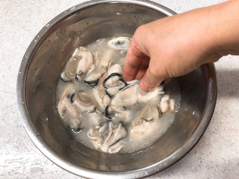 ボウルに牡蠣、片栗粉、塩を入れ、かぶるくらいの水を注ぎ、手で混ぜ、数分置く